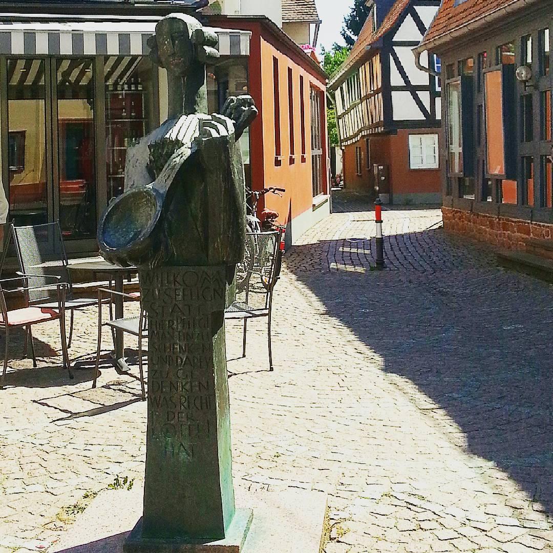 Der Löffeltrinker erinnert an die alte Tradition, dass Händler in Seligenstadt freies Geleit erhielten, wenn sie es schafften, den großen Löffel gefüllt mit Wein in einem Zug leer zu trinken. Für viele war Seligenstadt der letzte Halt vor Frankfurt auf dem Weg zur Messe