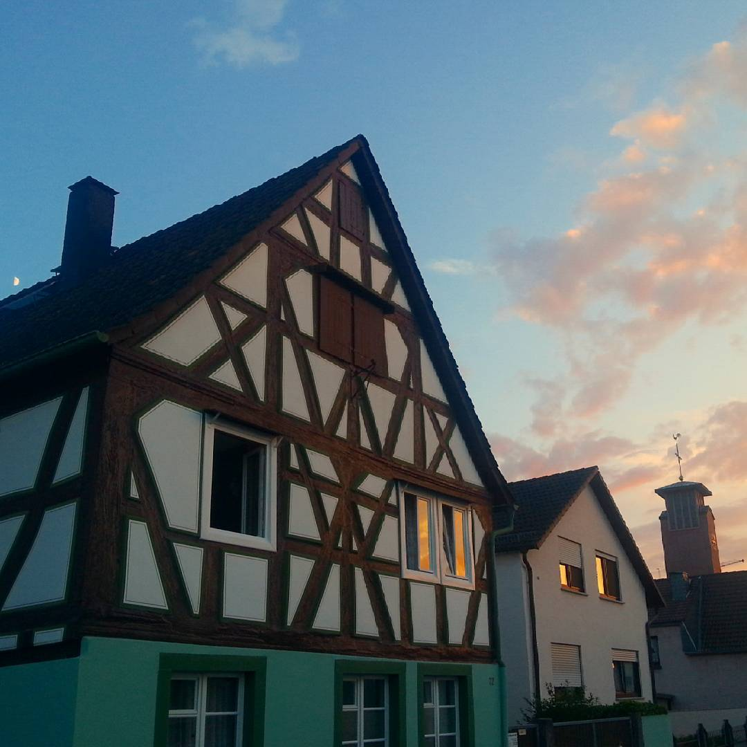 Kunstvolles Fachwerk gibt es nicht nur im Seligenstädter Stadtkern. Auch in Klein-Welzheim findet man beispielsweise dieses schöne Fachwerkhaus. Im Hintergrund sieht man den Kirchturm, den Mond und einen leuchtenden Abendhimmel