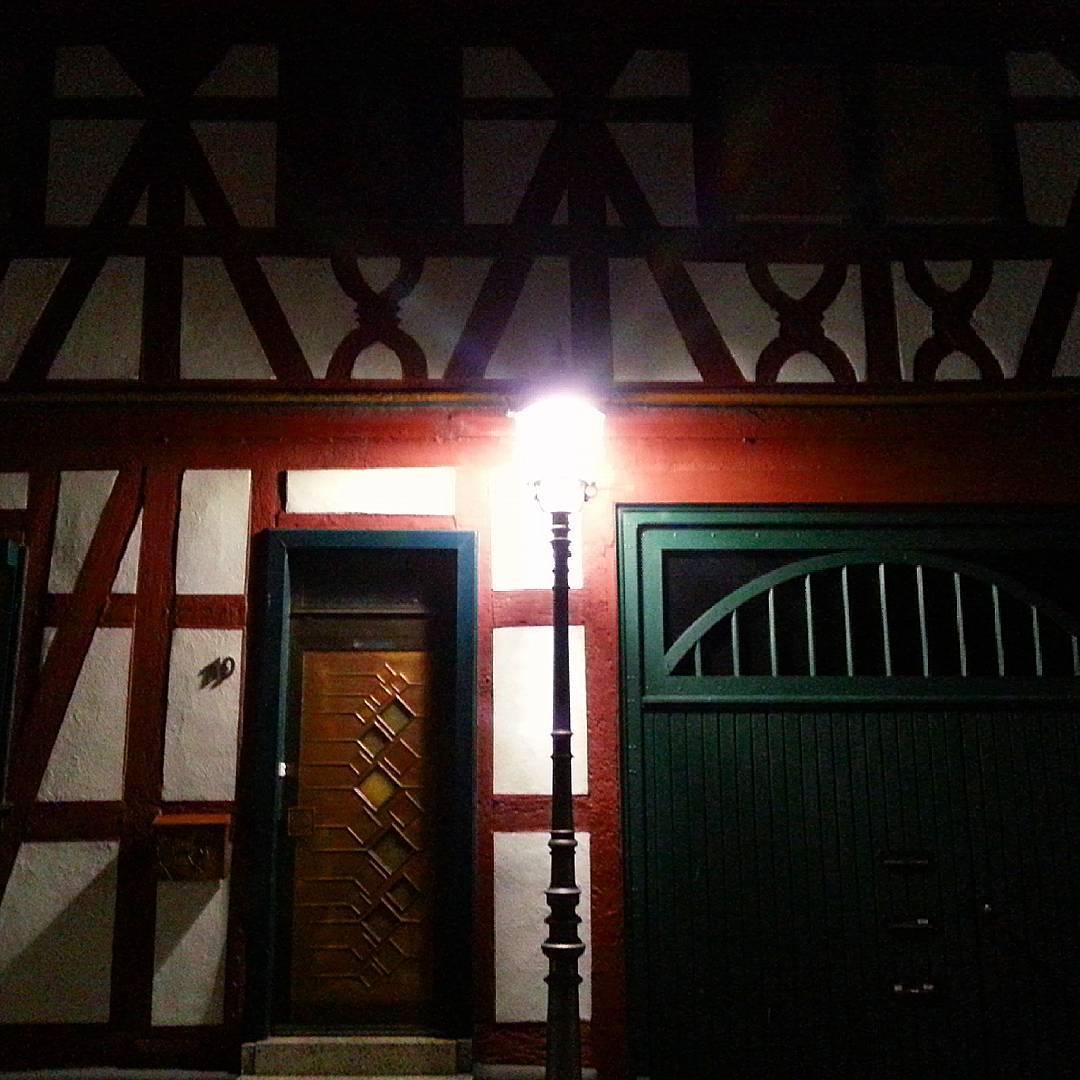 Eine Straßenlaterne in der Altstadt vor einem stimmungsvoll angeleuchteten Fachwerkhaus