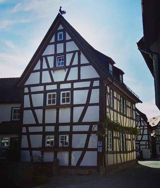Mehrstöckiges Fachwerkhaus in der seligenstädter Altstadt und oben auf dem Dach ein Hahn