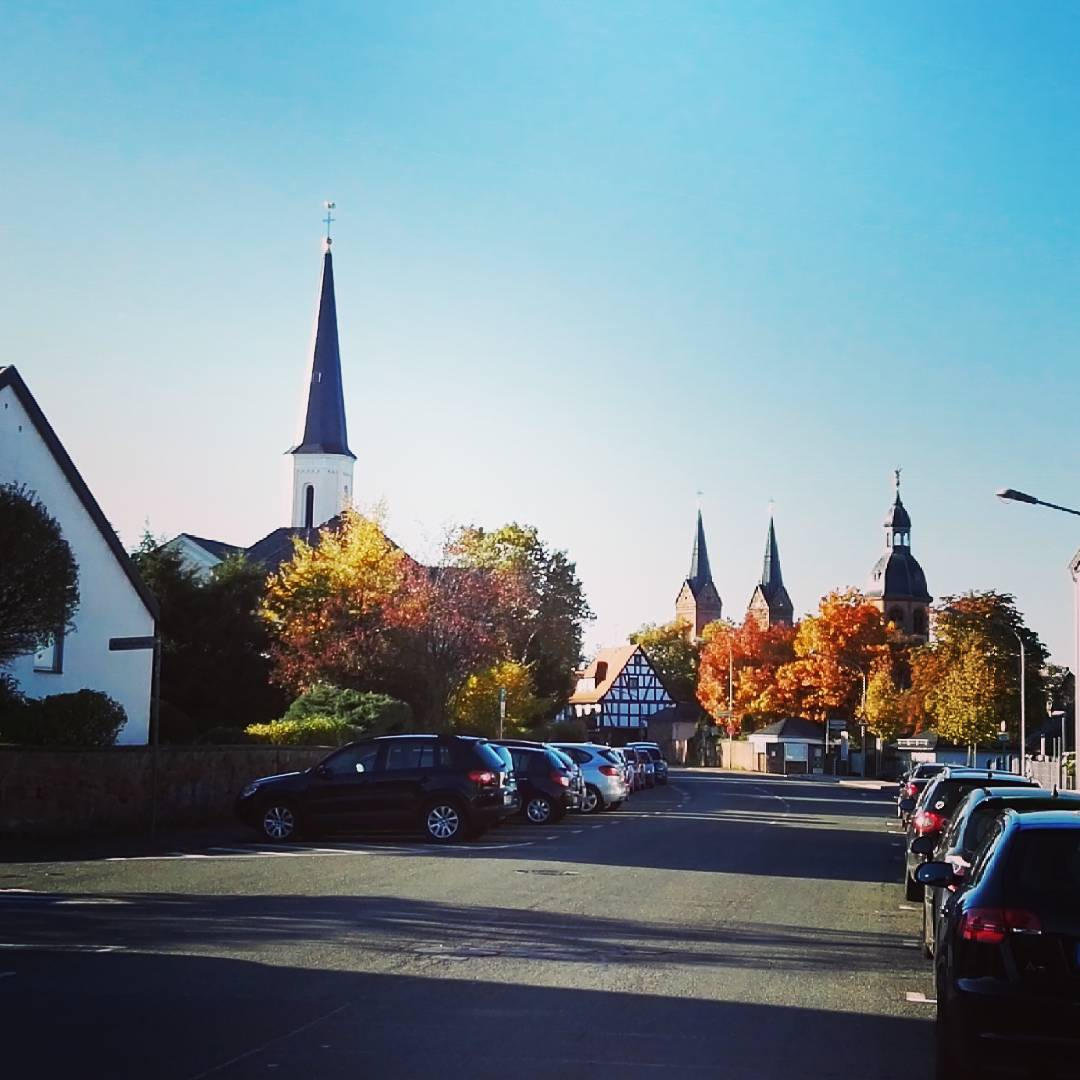 Die Kirchtürme Seligenstadts hinter herbstlichen Bäumen